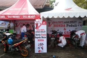 Mekanik Honda melakukan service gratis sepeda motor untuk korban musibah banjir di Pulau Jawa dan Manado